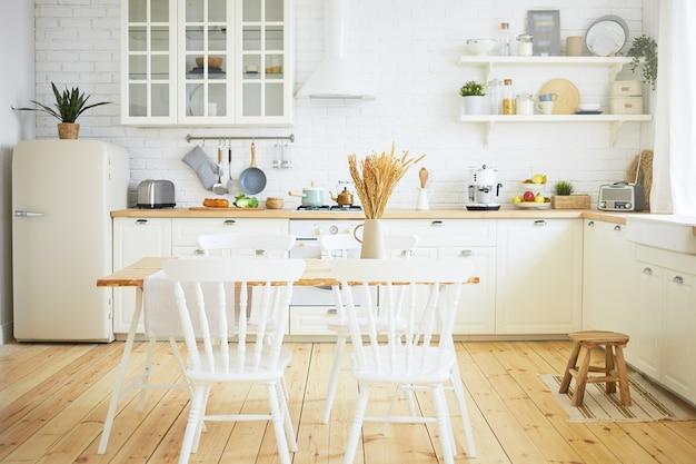 Intérieur de cuisine scandinave élégant: chaises et table au premier plan, réfrigérateur, long comptoir en bois avec machines, ustensiles sur étagères. intérieurs, design, idées, concept de maison et de confort