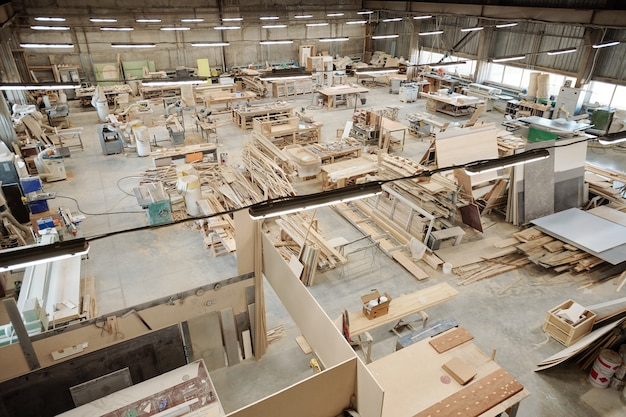 Intérieur du grand atelier d'usine de meubles contemporains avec des postes de travail composés d'établis avec des fournitures de travail