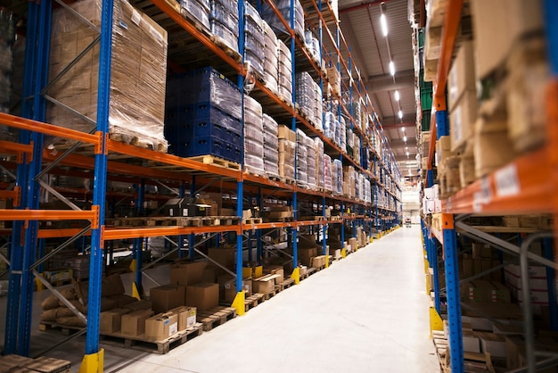 Intérieur du grand entrepôt de distribution avec des étagères empilées avec des palettes et des produits prêts pour le marché