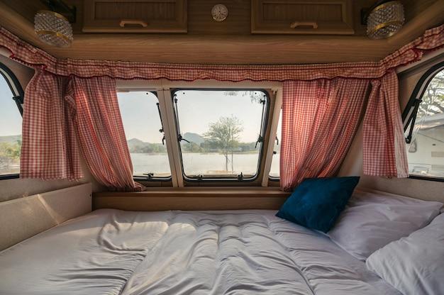 À l'intérieur du lit vide dans le camping-car et la vue à travers la fenêtre avec rideau au bord du lac