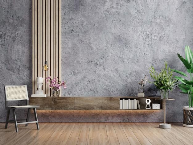 L'intérieur du salon a une armoire pour la télévision et une chaise dans une salle de ciment avec un mur en béton.