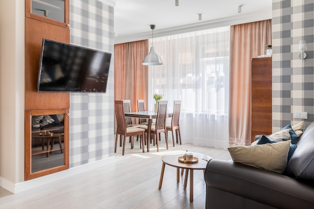 Intérieur du salon et de la cuisine avec un canapé, une télévision et une grande fenêtre derrière les rideaux. il y a du papier peint dans une cage sur les murs.