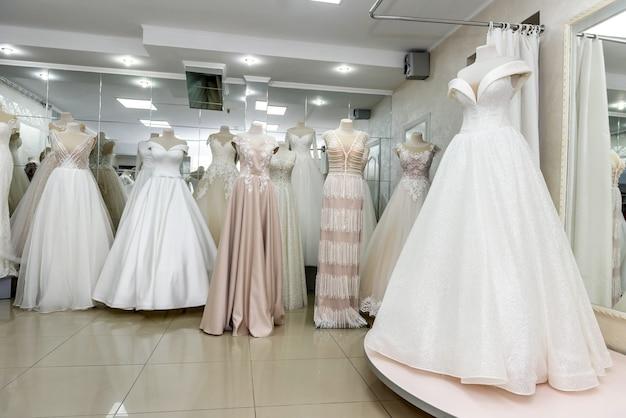 Intérieur du salon de mariée, robes de mariée sur mannequins