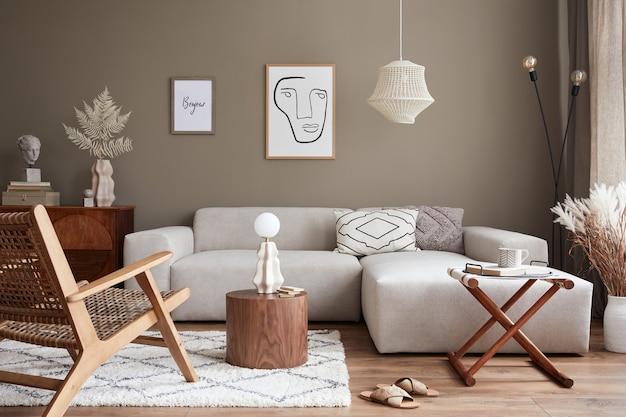 Intérieur élégant avec canapé modulaire design neutre, cadres d'affiches maquettes, fauteuil en rotin, tables basses, fleurs séchées dans un vase, décoration et accessoires personnels élégants dans un décor moderne