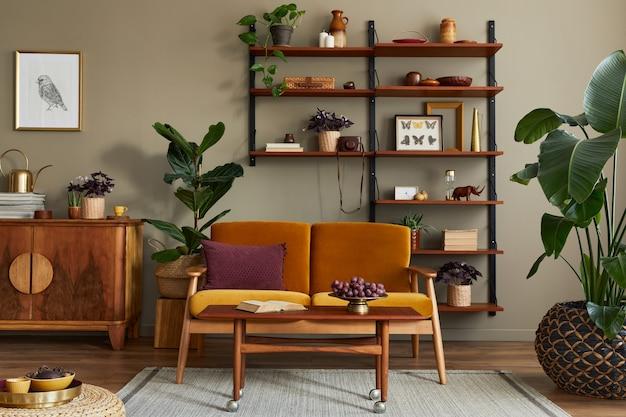 Intérieur élégant du salon avec canapé jaune miel, bibliothèque en bois, plantes, commode, cadre photo, tapis, décoration et accessoires élégants dans la décoration intérieure.