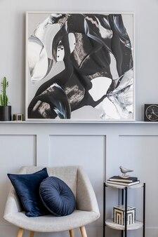 Intérieur élégant du salon avec fauteuil design gris, oreillers, tabouret en marbre, peintures, cactus, décoration, horloge noire et accessoires personnels élégants dans une décoration moderne.
