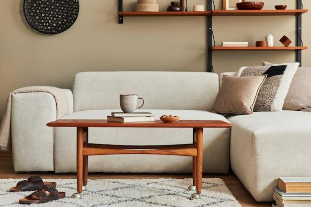 Intérieur élégant du salon avec table basse design en bois, canapé beige, tasse de café, livre, décoration et accessoires élégants dans un décor élégant.