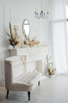 Intérieur élégant de la maison dans des tons blancs avec canapé vintage, lustre en cristal, miroir sous cheminée décoré de fleurs séchées.