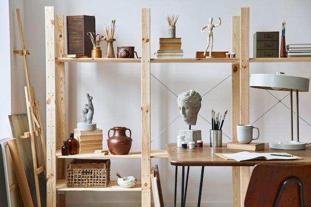 Intérieur d'espace de travail d'artiste unique avec bureau élégant, chevalet en bois, bibliothèque, œuvres d'art, accessoires de peinture, décoration et objets personnels élégants. salle de travail moderne pour artiste..