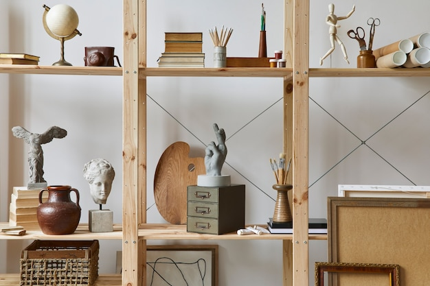 Intérieur d'espace de travail d'artiste unique avec bureau élégant, chevalet en bois, bibliothèque, œuvres d'art, accessoires de peinture, décoration et objets personnels élégants. salle de travail moderne pour artiste.