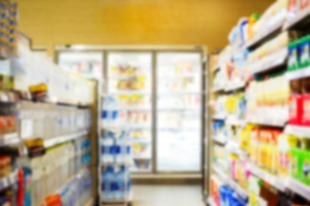 Intérieur flou du supermarché avec des produits de consommation sur une étagère.