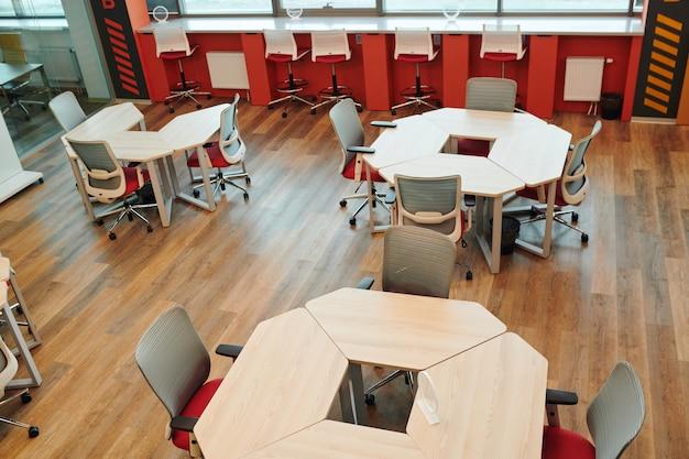 Intérieur d'un grand bureau à aire ouverte avec de nombreuses chaises par différents types de tables contre zone de repos avec canapé et coussins sans personne autour