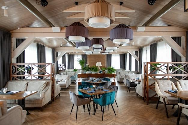 Intérieur de la grande salle du restaurant de luxe moderne avec des tables servies et confortables canapés et fauteuils en velours doux autour
