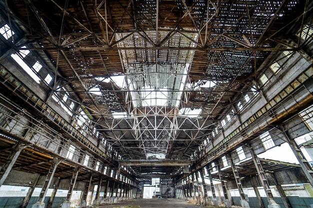 Intérieur industriel léger d'un immeuble ancien aux plafonds et murs endommagés.