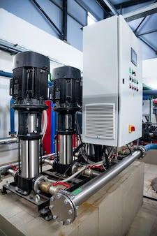 Intérieur industriel de la pompe à eau, vannes, manomètres, moteurs à l'intérieur de la salle des machines. vanne et pompes dans une salle industrielle. pipelines et pompes puissants modernes urbains, systèmes de contrôle automatique