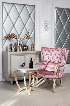 Intérieur de luxe. fauteuil luxueux en velours rose, meubles anciens sculptés, intérieur classique. vin servi dans un restaurant élégant en attente d'un invité.