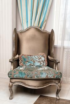 Intérieur de luxe. fauteuil marron luxueux, meubles anciens sculptés, détail intérieur classique de la pièce.