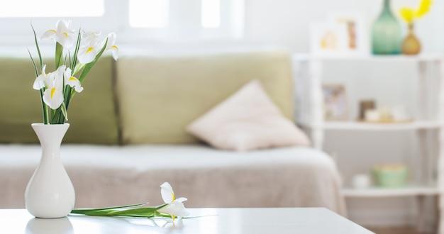 Intérieur de la maison blanche avec des fleurs de printemps et des décorations