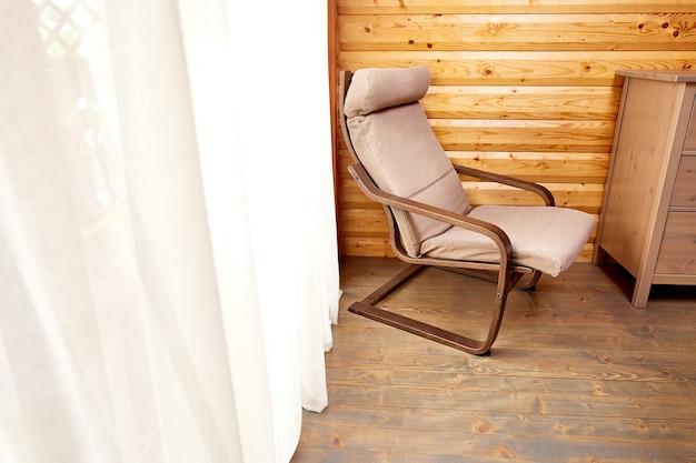 Intérieur de maison en bois. chaise confortable près de la fenêtre avec des rideaux élégants dans la chambre