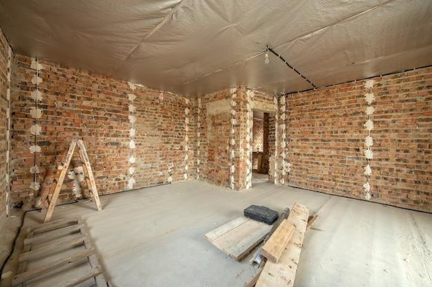 Intérieur de maison en brique inachevée avec sol en béton et murs nus en construction.