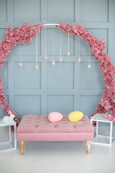 Intérieur de la maison avec canapé rose grande couronne de sakura sur mur décor de pâques du salon