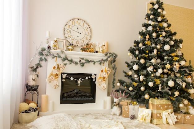 Intérieur de maison décoré de noël avec cheminée, horloge murale, arbre de noël et cadeaux en dessous. joyeux noël et concept de nouvel an.
