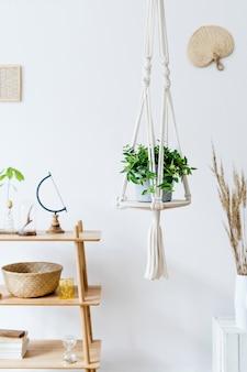Intérieur de maison élégant et bohème d'un espace ouvert avec bureau en bois, chaise, lampe et étagère blanche. accessoires personnels design et élégants. botanique et minimaliste. décoration de maison. peinture abstraite sur le mur