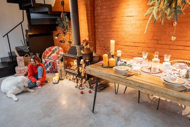 Intérieur de maison élégant avec table à manger et cheminée à la décoration festive. femme avec un chien pendant les vacances du nouvel an