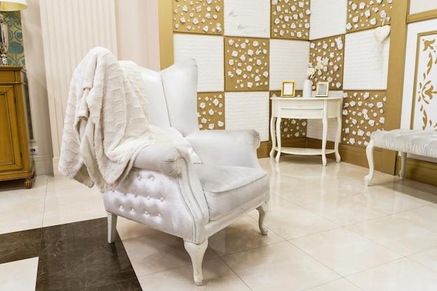 Intérieur de maison de luxe dans des tons clairs avec un beau fauteuil matelassé blanc