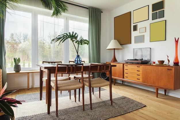 Intérieur de maison scandinave moderne du salon avec mobilier design rétro, palmier tropical, mur de galerie, décoration et accessoires personnels élégants dans un décor élégant.