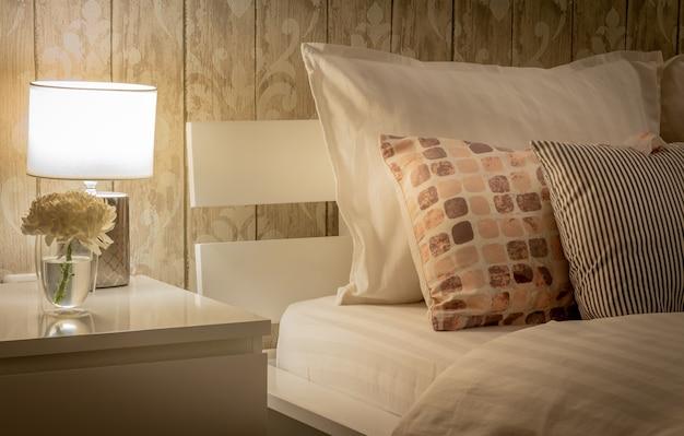 Intérieur de maison vintage avec cadre de chambre, y compris table de chevet avec lampe. jeu de couleurs gris. literie de style satiné