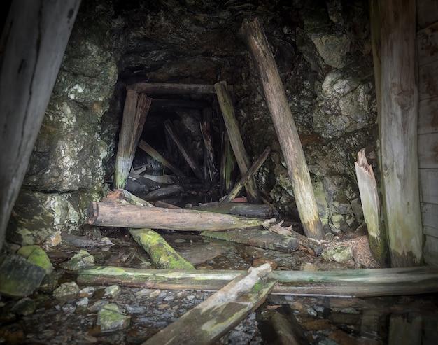 Intérieur de la mine abandonnée. tunnel souterrain sombre avec des supports en bois pourris