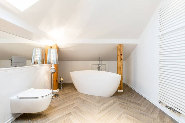 Intérieur moderne et blanc de salle de bain mansardée avec baignoire ovale en céramique, radiateur mural et poutres apparentes