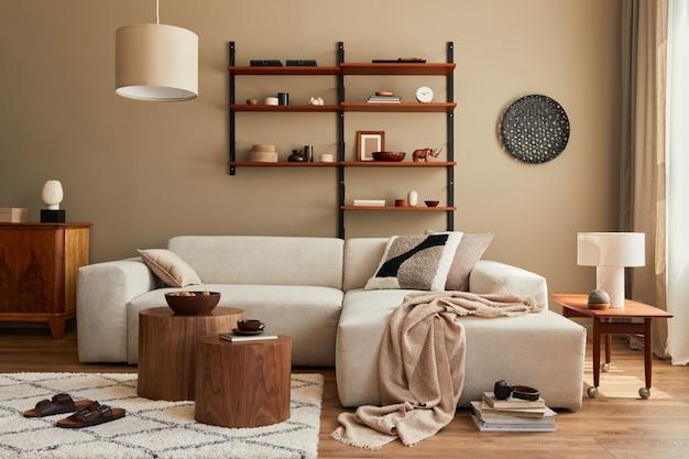 Intérieur moderne du salon avec canapé beige modulable design, table basse, meubles, suspension, étagère, chaussons, tapis, décoration et accessoires personnels élégants dans la décoration intérieure.