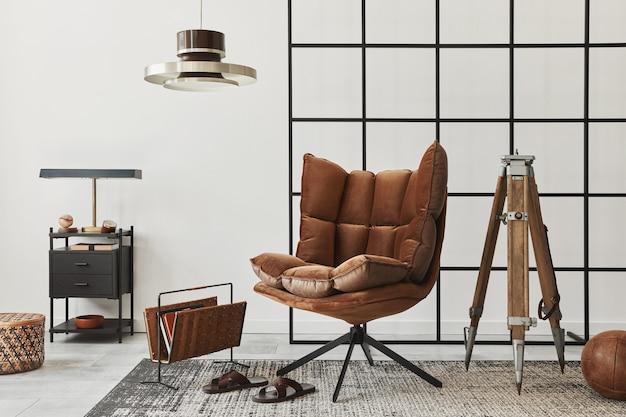 Intérieur moderne du salon avec fauteuil marron design, table d'appoint, lampe à suspension, mur de loft, chaussons, tapis, décoration et accessoires personnels élégants dans la décoration intérieure.