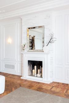 Intérieur moderne d'un grand salon luxueux et lumineux. canapé blanc coûteux et étagères en bois, murs blancs avec moulures et lustre luxueux