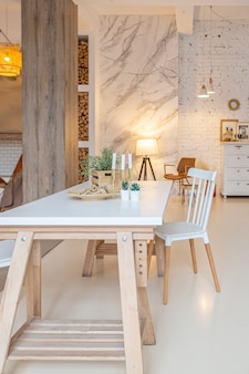 Intérieur moderne à la mode d'un studio lumineux avec des colonnes en bois de style loft, décoré de briques, de marbre et de bois avec des meubles élégants et des murs blancs