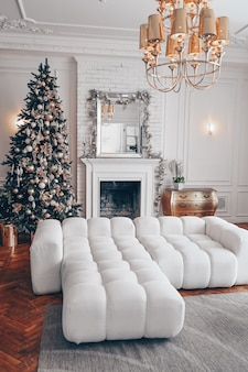 Intérieur moderne de salon blanc avec des éléments classiques et arbre décoré de noël