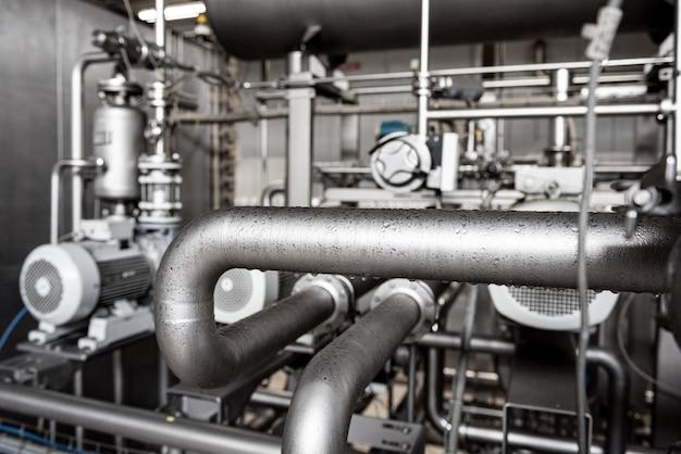 Intérieur moderne d'une usine de boissons avec barils et tuyaux