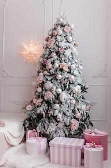 Intérieur de noël décoré sapin décoré de guirlandes avec des coffrets cadeaux dans une salle blanche décor