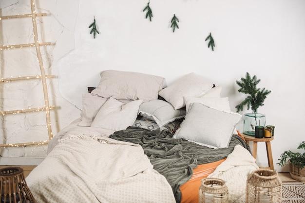 Intérieur de noël moderne de la chambre avec des oreillers et des branches de couverture