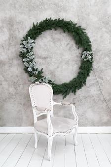 Intérieur de noël de la pièce. une chaise grise se dresse sous un mur lumineux sur lequel est suspendue une couronne de noël. couronne de conifères vert décorée de feuilles et guirlandes d'argent.