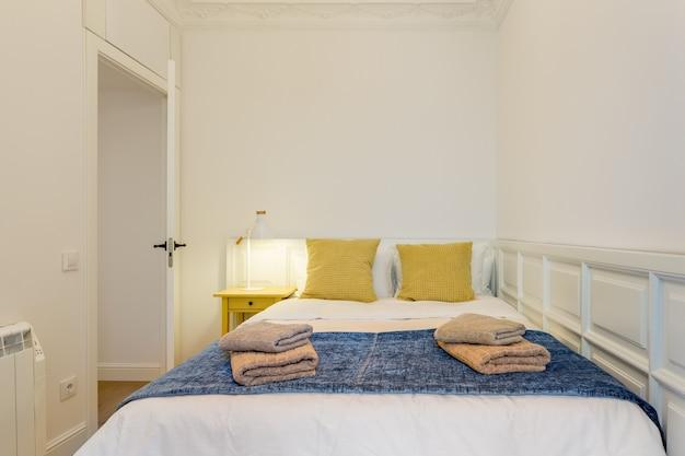 Intérieur des oreillers jaunes de la chambre touristique sur le lit avec des serviettes un appartement prêt à être réservé pour...