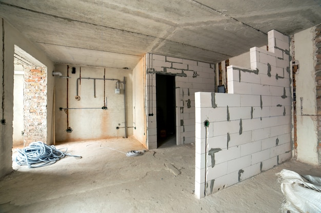 Intérieur d'une pièce avec murs et plafond nus en construction.