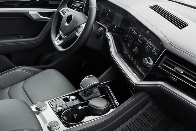Intérieur d'une prestigieuse voiture noire moderne. sièges et accessoires confortables en cuir et volant