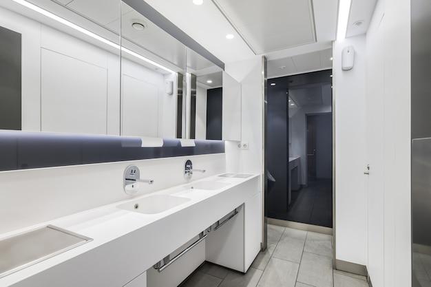 Intérieur public ou de bureau des toilettes pour hommes avec lavabos et grand miroir salle de bain design moderne en blanc...