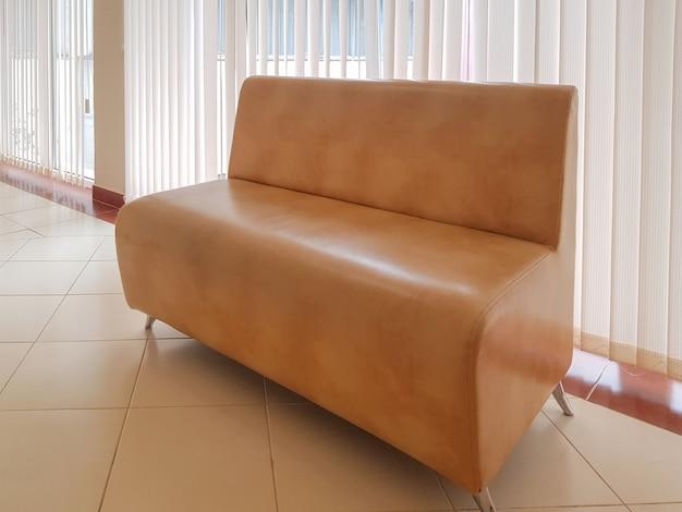 Intérieur résidentiel d'un salon moderne avec un canapé et une fenêtre panoramique avec stores ou bureau