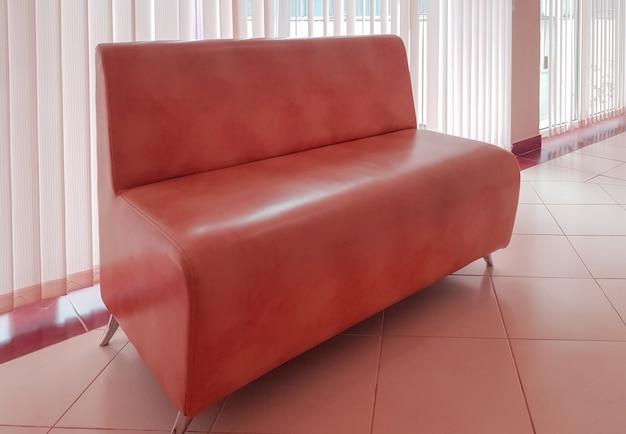 Intérieur résidentiel d'un salon moderne avec un canapé rose et une fenêtre panoramique avec stores ou bureau