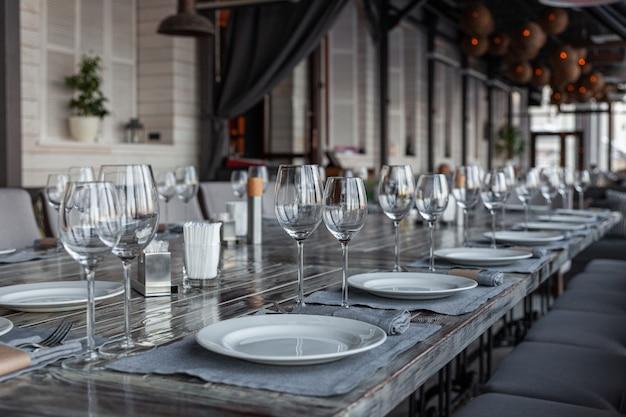 Intérieur de restaurant véranda moderne, cadre de banquet, verres, assiettes