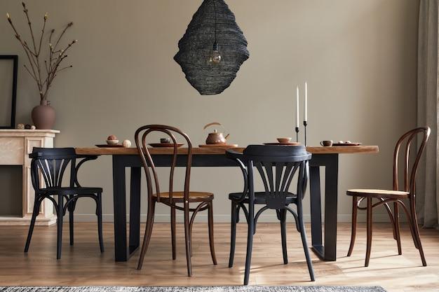 Intérieur rustique élégant de la salle à manger avec table en bois de noyer, chaises rétro, décoration, cheminée, fleur séchée, cadre photo chandelier et tapis dans un décor minimaliste.